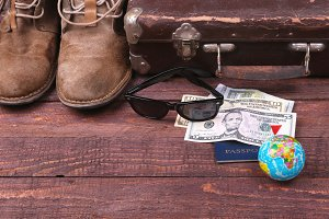 Travel concept with Vintage suitcase, sunglasses, old camera, suede boots, case for money and passport on wooden floor.