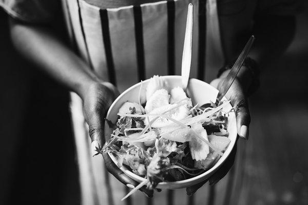 Black woman holding a salad bowl