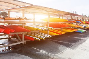In sunlight, red, yellow and white kayaks placed upside down on metal storage racks. Stocked canoe in the Brest, France 28 May 2018
