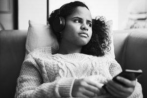 Woman listening to music on sofa