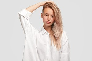 Pleasant looking gorgeous female model with long fair hair combed on one side, wears man`s white shirt, has pure skin, keeps hand behind head, shows natural beauty, isolated on white background