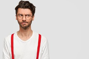 Bearded handsome guy with suspicious thoughtful expression, looks aside, has gloomy expression, wears glasses and elegant clothes, stands against white background with copy space for advertisement