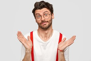 Horizontal shot of hesitant young Caucasian male has puzzled and doubtful expression, raises palms and looks in puzzlement, has ignorant look, wears glasses and white shirt with red suspenders