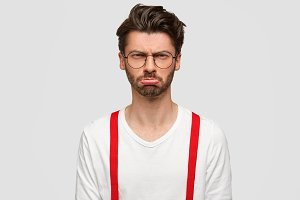 Photo of displeased sullen unshaven male manager angry as has much work, needs good rest, has sullen expression, wears elegant white shirt with red suspenders. People and negative feeling concept