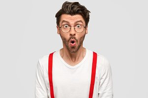 Horizontal shot of horrified young Caucasian male has shocked scared look, worries as hears bad news, wears spectacles and white shirt with red suspenders, stares with big eyes, poses in studio