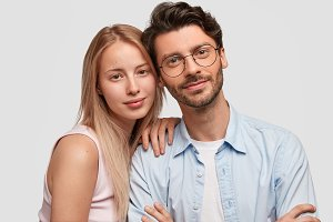 Portrait of lovely couple embrace each other, have good relationship, look positively directly at camera, happy to find out that they are expecting child, think about future. People and family concept