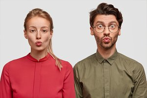 People, friendship and facial expressions concept. Lovely young female model in red blouse stands near hipster male, keep lips round and make grimace while being photographed for youth magazine
