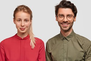Photo of lovely young female in red blouse meets with her older brother, feels support near his strong shoulder, pose together against white background. Glad young male professor with student