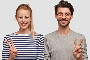Happy young couple smile and gesture vsigns, being in high spirit, make photo for long memory, enjoy vacation together, dressed in casual sweaters isolated on white wall. Woman and man show peace sign