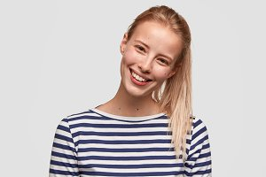 Happy female student with broad smile, has light hair combed in pony tail, recieves positive news, dressed in striped casual jacket, glad to meet with best friend, isolated on white background