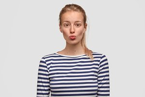 Lovely young female pouts lips and has appealing appearance, dressed in sailor casual sweater, spends leisure time in family circle, isolated over white background. People and facial expressions