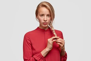 Waist up portrait of serious beautiful female does plait from her long hair, dressed in red blouse, models in white studio. Pretty woman model comes in beauty salon. People, lifestyle, youth concept