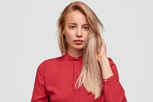 Portrait of attractive light haired female customer tries on new red blouse in luxury boutique, spends money on clothes, has healthy skin and pleasant appearance. Friendly European woman isolated