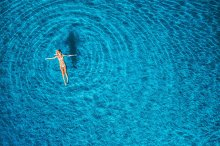 Aerial view of swimming woman in mediterranean sea at sunset by  in Holidays