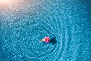 Aerial view of young woman swimming in the sea with transparent