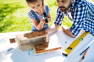 Father with a small daughter outside, making wooden birdhouse.