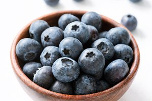 Blueberries in wooden bowl on white
