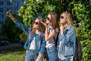 Three teenage girls in summer outdoors. Makes a photo of the person on phone. They wear stylish jeans clothes. Sunny protective glasses. Teenage girls are blondes with backpacks behind their backs.