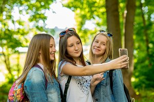 Girls schoolgirls in summer in a park in fresh air. Makes photos pose on the camera. Outdoors in the shade of trees. They are dressed in casual clothes. Pupils are on vacation.