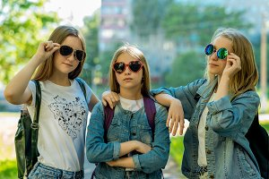 Three girls are little teenagers. In summer park fresh air. Little schoolgirls are posing on camera in sunglasses. They are dressed casual clothes. Best Friends in th classroom. Friendship of girls.