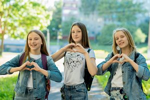 Girls teenagers in summer in the park in fresh air. Gesture hands show the heart of love. Dressed in casual clothes. The best friends of the teenage girlfriend. Rest after school.