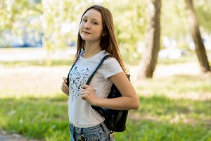 Beautiful teen girl in summer in a park outdoors in shade of a tree. Dressed in casual clothes. Behind the backpack. The schoolboy is going to school.