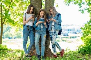 Three teenage girls stand by tree in summer in park. In his hands holds smartphone and communicates social networks. Corresponds with parents concept of internet addiction. Friendly communication.
