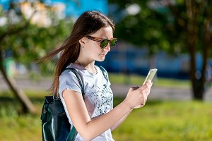 The brunette girl in sunglasses. In the summer in open air. Behind the backpack. In his hands holds a smartphone. Corresponds with friends. The teenager after school is on break.