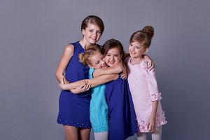 Group happy smiling young teen girls hugging. Friendly embrace of happy,cheerful children. Stylish elegant four children posing at studio in beautiful blue dresses for catalog children's clothes.