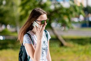 A teenage girl is talking on the phone. In the summer in the park in nature. Brunette in sunglasses. A schoolgirl after school. Emotional happy Smiling in conversation .