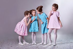 Group little girl in beautiful pink,blue dresses.Fashionable 4 people lady children together,advertise clothes for catalog fashion design collection.Four girlfriends holding lollipop,gray background.