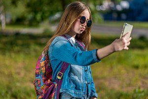 Little girl is blonde. In summer park fresh air. Behind back is a beautiful backpack. In hands holding a smartphone makes a photo. Make a video call with parents. Communication in social networks.