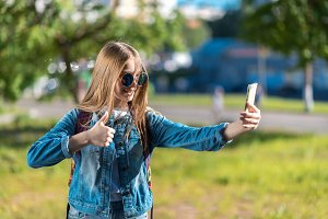 The girl is blonde. A little teenager after school. In summer in park in fresh air. In his hands holds a smartphone. A gesture of hands shows a thumbs up class. Video call with parents on smartphone.