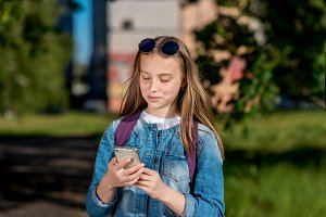 A teenage girl is holding hands with a phone. Happy smiling is writing in social networks. In summer in the open air. Bright sunny day on the head of sunglasses.
