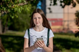Teenage girl brunette in summer a park outdoors. Holds the hands of the phone. He looks closely at the frame. Call parents after school. Waiting for a message to the phone.