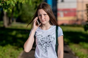 The brunette girl. In the summer in the park in the fresh air. He talks on the phone. Emotions a serious conversation. Find out the relationship by phone with parents after school.