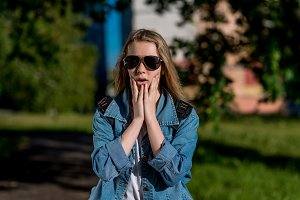 The teenage girl is surprised. Summer in the park in the fresh air. A bright sunny day in sunglasses. Gesture with his hands closing his cheeks. Emotions of fear of horror and misunderstanding.