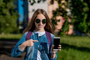 A teenage girl on a bright sunny day with sunglasses. In the summer in the park in the fresh air. In his hands holds a smartphone. With a gesture of his hand he points to the phone with his finger.