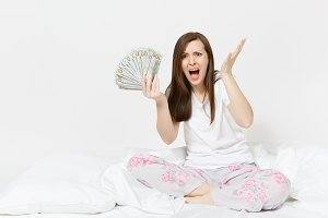 Young screaming sad woman sitting in bed with white sheet, pillow, wrapping in blanket on white background. Beauty female holding bundle of dollars, cash money in room. Rest, relax, good mood concept.