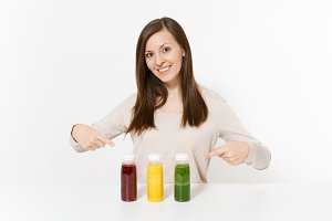 Young woman at table with green, red and yellow detox smoothies in bottles isolated on white background. Proper nutrition, vegetarian drink, healthy lifestyle, dieting concept. Area with copy space.
