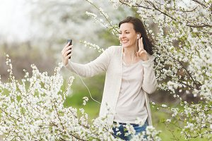 Young smiling woman in casual clothes with earphones listening music doing selfie on mobile phone showing victory sign in garden or park on blooming tree background. Spring flowers. Lifestyle concept.