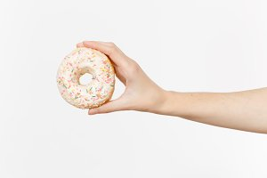 Close up female holds in hand colorful white donut isolated on white background. Proper nutrition or sweets, dessert fast food, dieting morning concept. Copy space for advertisement. Advertising area.