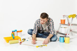 Young man sitting on floor with wallpaper roll, pencil, instruments for renovation apartment room isolated on white background. Wallpaper, gluing accessories, painting tools. Repair home concept.