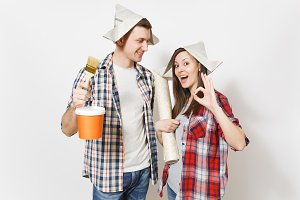 Young happy woman, man in casual clothes holding paint brush, paint bucket and wallpaper roll. Couple isolated on white background. Instruments for renovation apartment room. Repair home concept.