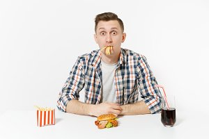 Fun hungry young man eating french fries, sitting at table with burger, cola in glass isolated on white background. Proper nutrition or American classic fast food. Advertising area with copy space.