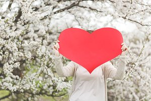 Young woman in casual clothes holding covering face with big red heart standing in city garden or park on blooming tree background. Copy space for advertisement. Spring flowers. Lifestyle concept.