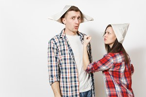Young dissatisfied woman, man in casual clothes and newspaper hats quarrelling. Couple isolated on white background. Instruments, accessories for renovation apartment room. Repair home concept.