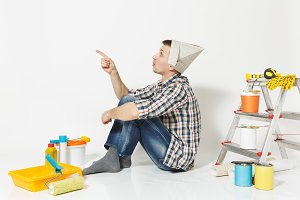 Young man in newspaper hat sitting on floor with instruments for renovation apartment room isolated on white background. Wallpaper, gluing accessories, painting tools. Repair home concept. Side view.
