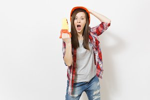 Irritated shocked woman in protective construction orange helmet holding toy saw and clinging to head isolated on white background. Instruments for renovation apartment room. Repair home concept.