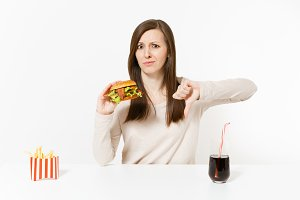 Sad woman showing thumbs down at table with burger, french fries, cola in glass bottle isolated on white background. Proper nutrition or American classic fast food. Advertising area with copy space.